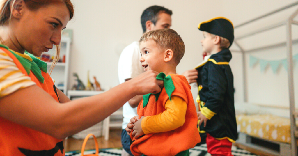 A mom and her baby dressed up in pumpkin costumes for a family Halloween party.