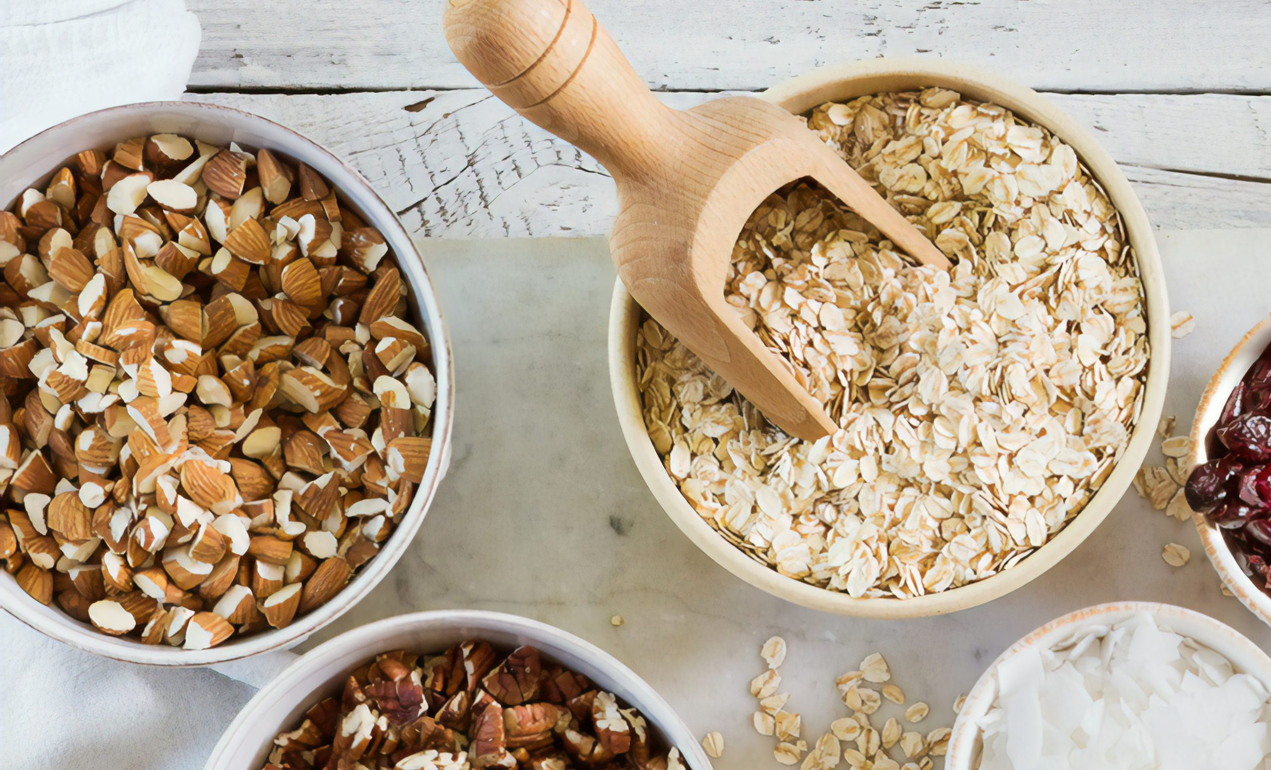 A variety of galactagogues, such as oats, coconut, flax, and almonds on a table