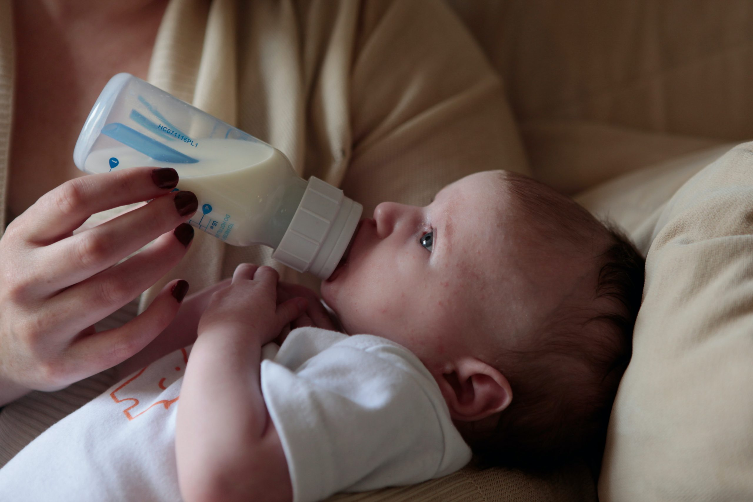 A mother feeding her baby from a bottle of milk.